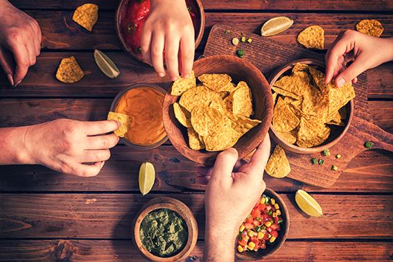 Snacks, viele Hände greifen zu Nachos   ÓNIRO essen